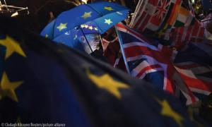 An anti-Brexit protester stands with an illuminated EU umbrella surrounded in flags outside the Houses of Parliament in London