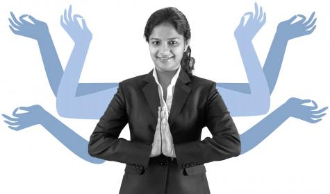 A young professional  Indian woman greeting with 'Namaste'.